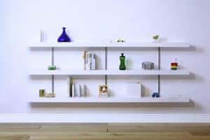 White floating shelves in a living space against a white wall with decorative pieces on the shelves