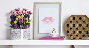 Image of a white shelf on a wall with decorative pieces.