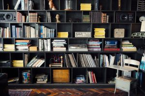 Image of a black bookshelf along a wall filled with books, board games, and decorative pieces